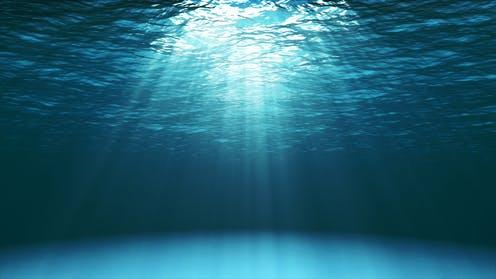 under water shining light over